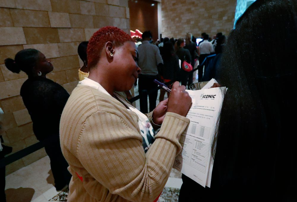 In this June 4, 2019 photo, job applicant Esta Williams, center, uses Tracy Simeton's back to fill out a questionnaire as they wait in line at the Seminole Hard Rock Hotel & Casino Hollywood during a job fair in Hollywood, Fla. On Friday, Aug. 2, the U.S. government issues the July jobs report. (AP Photo/Wilfredo Lee, File)