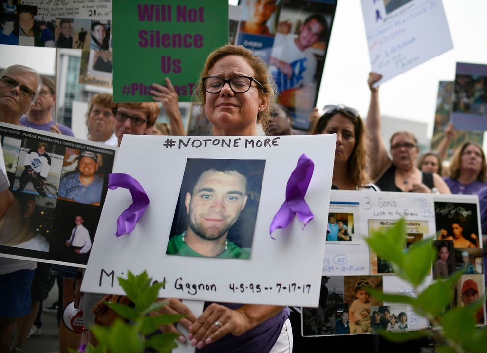 FILE - In this Aug. 17, 2018 file photo, Christine Gagnon, of Southington, Conn., holds a sign during a protest with others who have lost loved ones to OxyContin and opioid overdoses, outside the Purdue Pharma headquarters in Stamford, Conn. Gagnon lost her son Michael 13 months earlier. Nearly ten years ago, the blockbuster painkiller OxyContin was reformulated to discourage abuse by snorting and injecting, but it's unclear whether the harder-to-abuse format has decreased cases of addiction, overdose and death. (AP Photo/Jessica Hill, File)