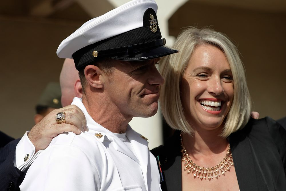 Navy Special Operations Chief Edward Gallagher, left, and his wife, Andrea Gallagher smile, after leaving a military court on Naval Base San Diego, Tuesday, July 2, 2019, in San Diego. A military jury acquitted the decorated Navy SEAL Tuesday of murder in the killing of a wounded Islamic State captive under his care in Iraq in 2017. (AP Photo/Gregory Bull)