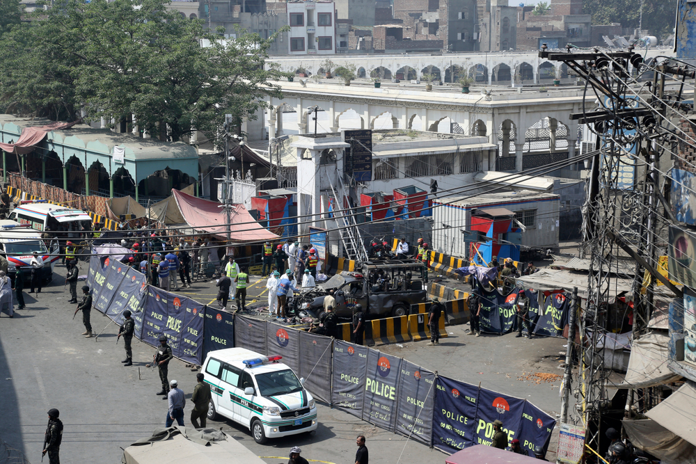 Pakistani security personnel cordon off a damaged police van in Lahore, Pakistan, Wednesday, May 8, 2019. A powerful bomb exploded near security forces guarding a famous Sufi shrine in Pakistan on Wednesday, police said. (AP Photo/K.M. Chaudary)