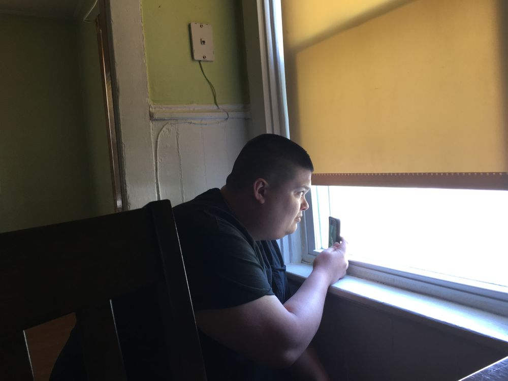 Brandon records a video out his apartment window.