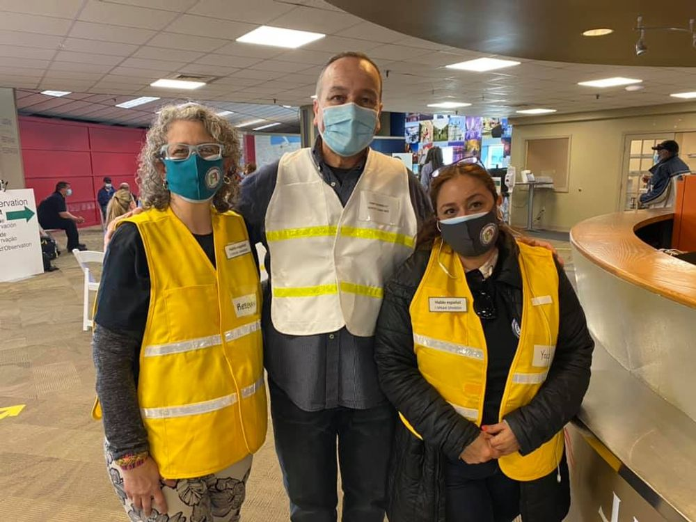 Rebekah Gomez (izquierda) y Yolanda Macías (derecha), de Conexión Latina Newport, posan en una clínica temporal para residentes latinos con Harp Donnelly, el jefe adjunto del Departamento de Bomberos de Newport.