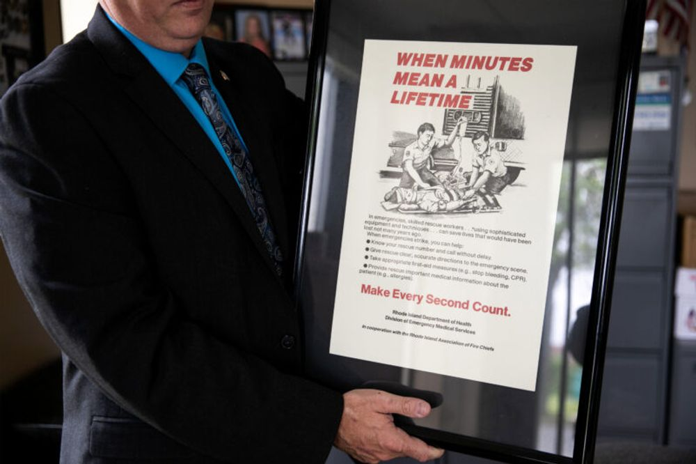 Jason M. Rhodes, chief of emergency medical services at the Rhode Island Department of Health, holds a vintage CPR poster in his office in Providence, Rhode Island.