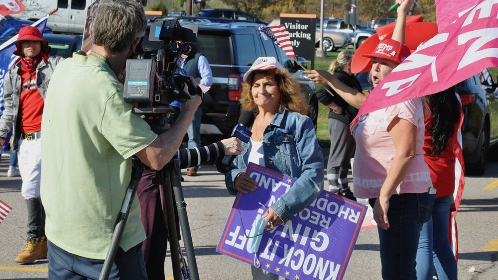 Supporters of Pres. Donald Trump being interviewed by a television news reporter outside the Rhode Island Board of Elections offices in Cranston on Friday, Nov. 6, 2020.