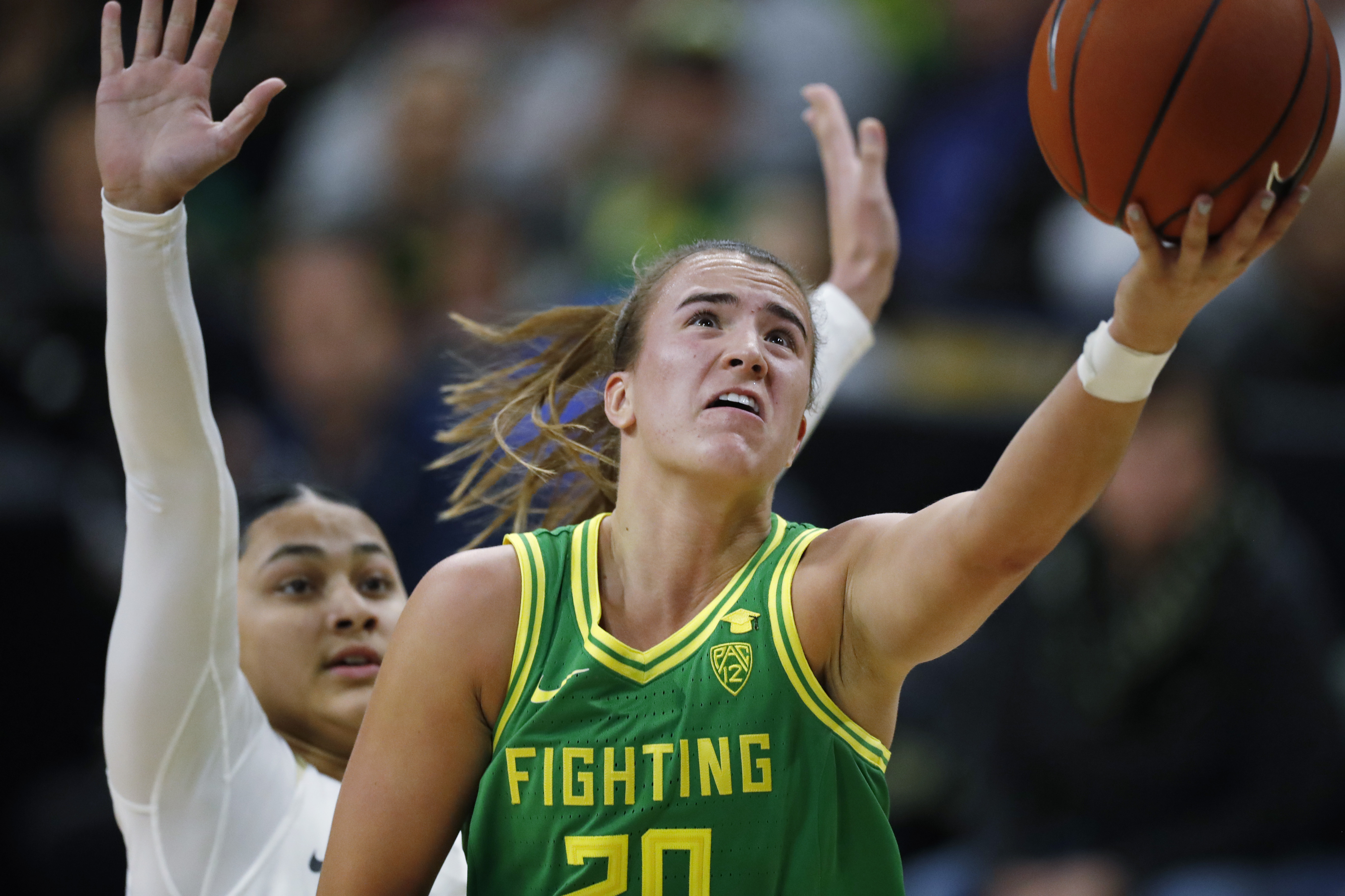 FILE - In this Feb. 1, 2020, file photo, Oregon guard Sabrina Ionescu, front, drives to the basket past Colorado guard Lesila Finau during the first half of an NCAA college basketball game in Boulder, Colo. Ionescu and Iowa wrestler Spencer Lee shared the Sullivan Award on Wednesday night, April 29, as the country's top amateur athlete. (AP Photo/David Zalubowski, File)