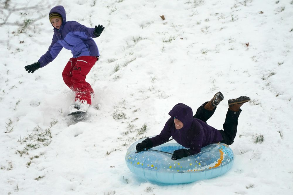 Krystal Krause, right, rides a tube and Lilyann Richard, 11, snowboards down a hill during a snowstorm, Wednesday, Dec. 16, 2020, in Lutherville-Timonium, Md. (AP Photo/Julio Cortez)
