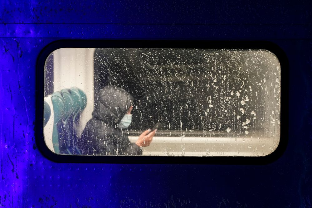 A passenger rides in a Long Island Rail Road train car as snow starts to fall Wednesday, Dec. 16, 2020, in the Queens borough of New York. (AP Photo/Frank Franklin II)