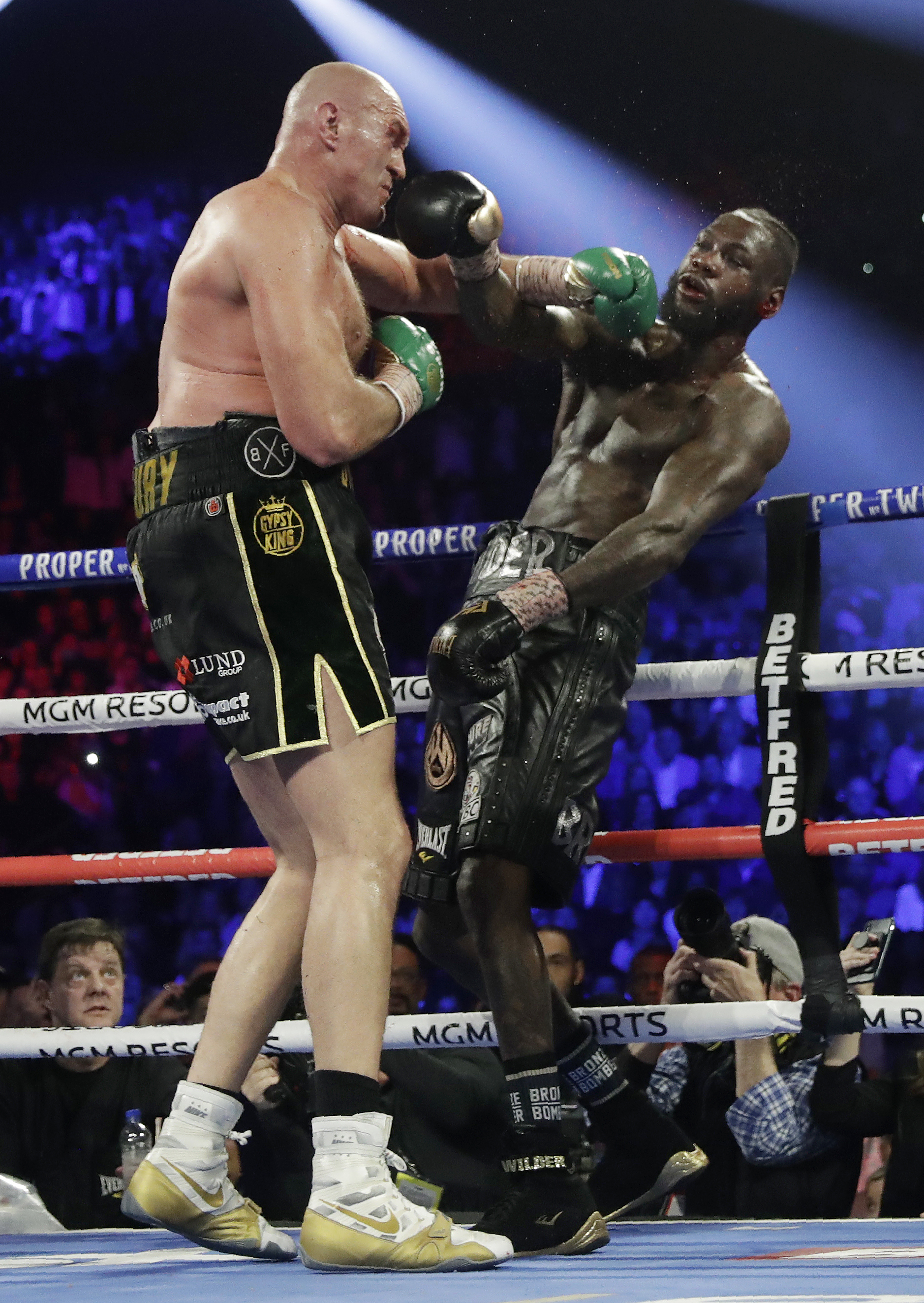 Tyson Fury, left, of England, lands a left to Deontay Wilder during a WBC heavyweight championship boxing match Saturday, Feb. 22, 2020, in Las Vegas. (AP Photo/Isaac Brekken)