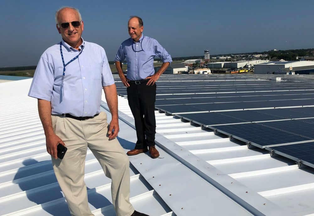 Cape Air founder and CEO Dan Wolf, right, and his brother Jim, the airline's director of sustainability, stand next to Cape Wind's own solar array.