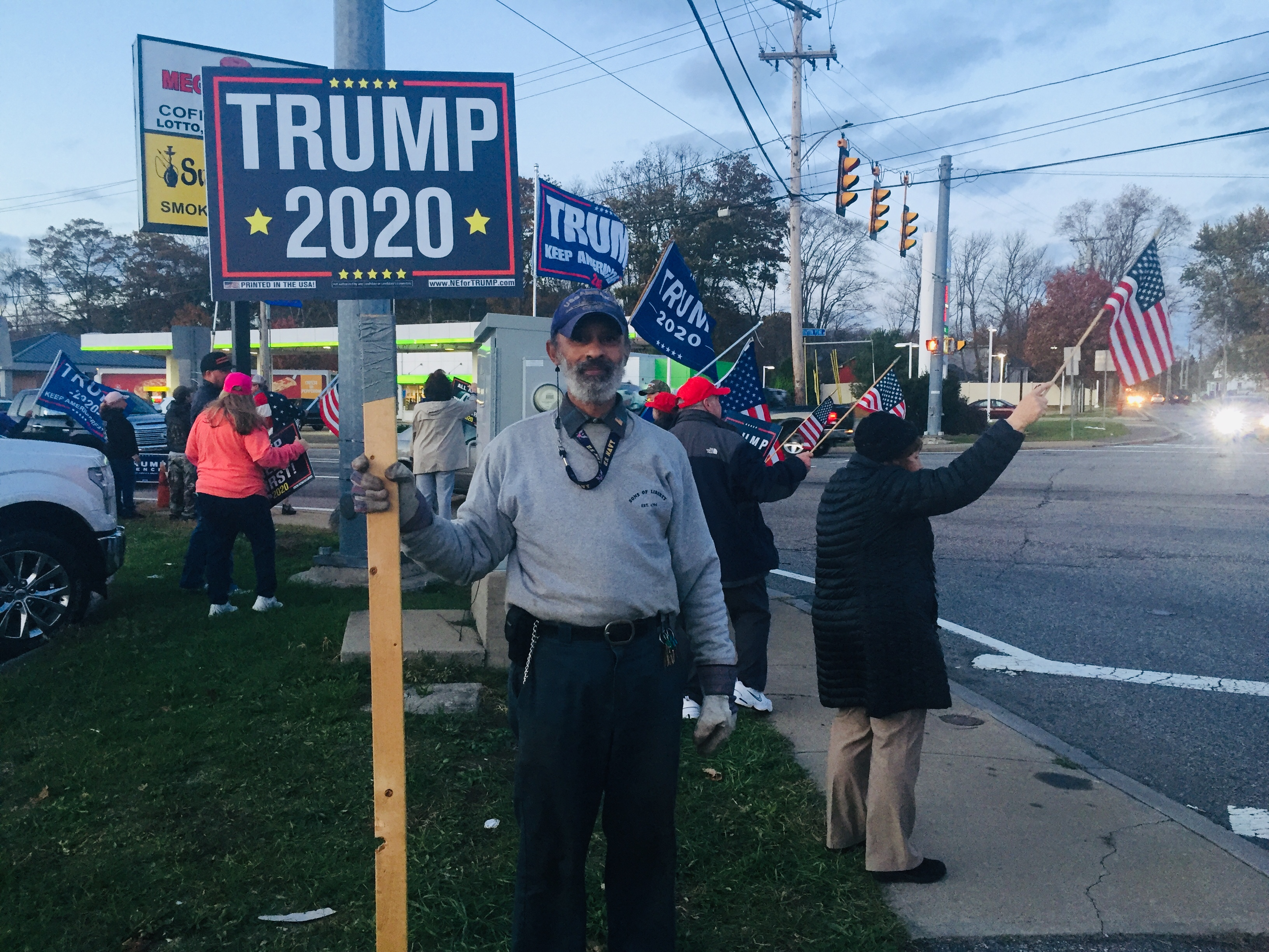 Joel, a supporter of President Trump, holds a sign during a standout outside of a Trump merchandise story in Somerset.
