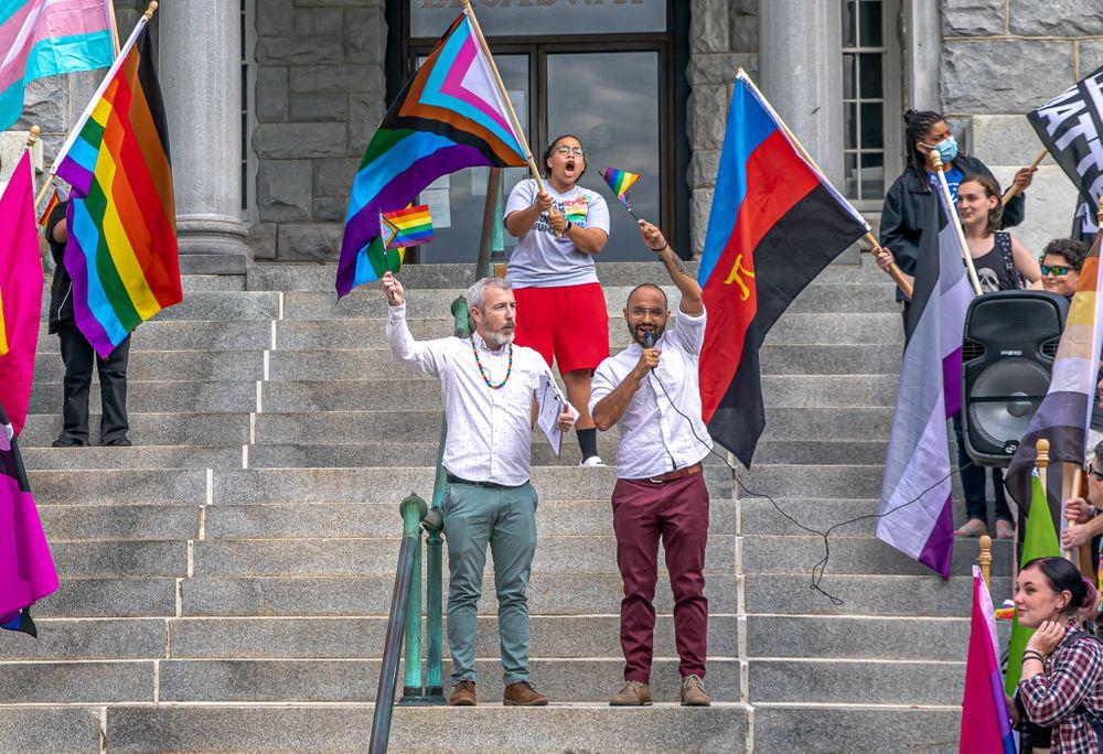 Sean O'Connor (left) and Daniel Cano Restrepo speak at a flag raising event at Newport City Hall.