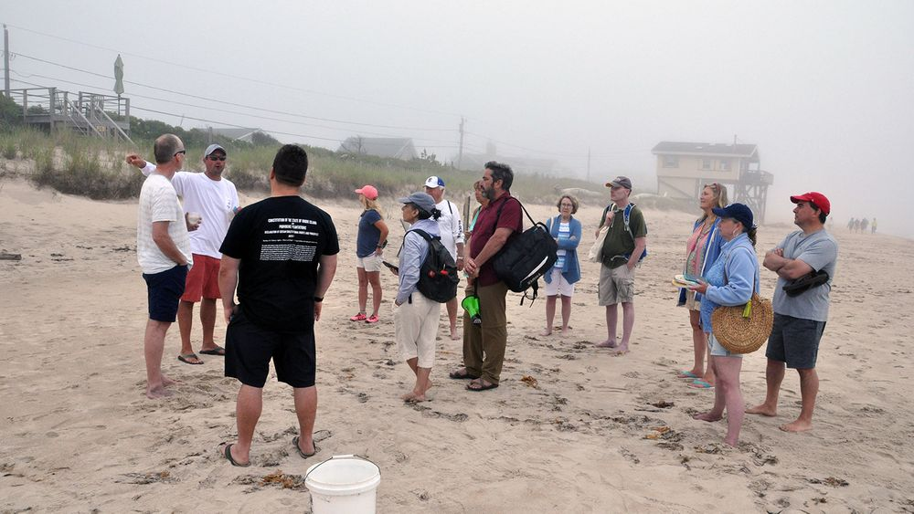 Property owner Keith Wilcox, second from left, speaks with shoreline rights advocates during a seaweed gathering protest, on June 26, 2021.