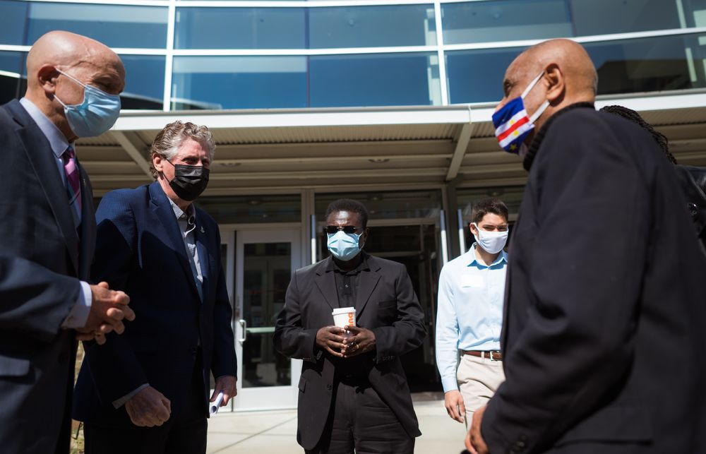 The Rev. Howard M. Jenkins Jr. (center) with Gov. Daniel J. McKee (left), Luis Daniel Muñoz (right) and Jim Vincent, president of the NAACP Providence Branch (far right) outside the Dunkin' Donuts Center vaccination clinic in April 2021