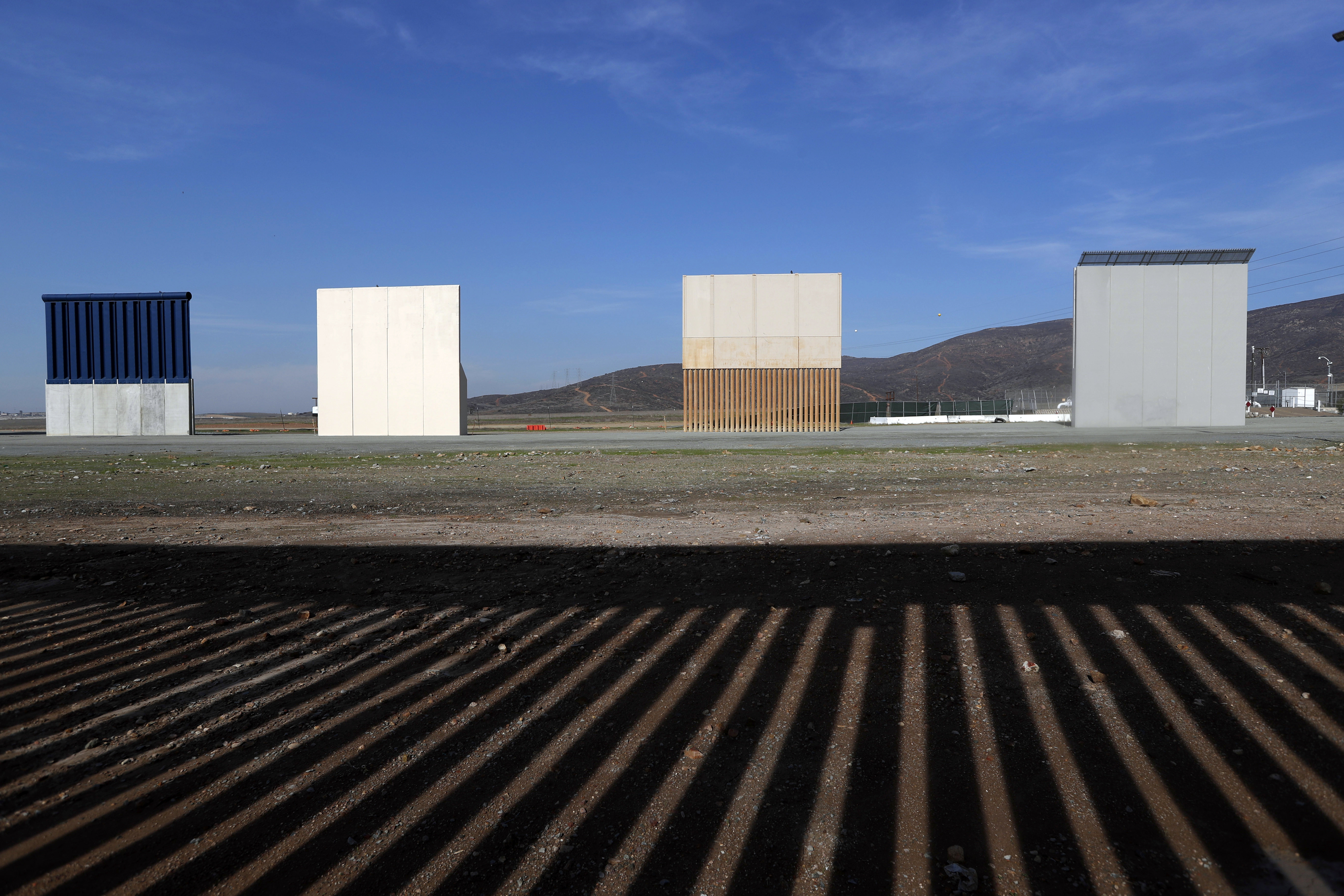 In this Wednesday, Dec. 12, 2018, file photo, border wall prototypes stand in San Diego near the Mexico-U.S. border, seen from Tijuana, Mexico, where the current wall casts a shadow in the foreground. Customs and Border Protection said Friday, Feb. 22, 2019, President Trump's eight border-wall prototypes will be torn down to make way for a secondary barrier separating California from Mexico.