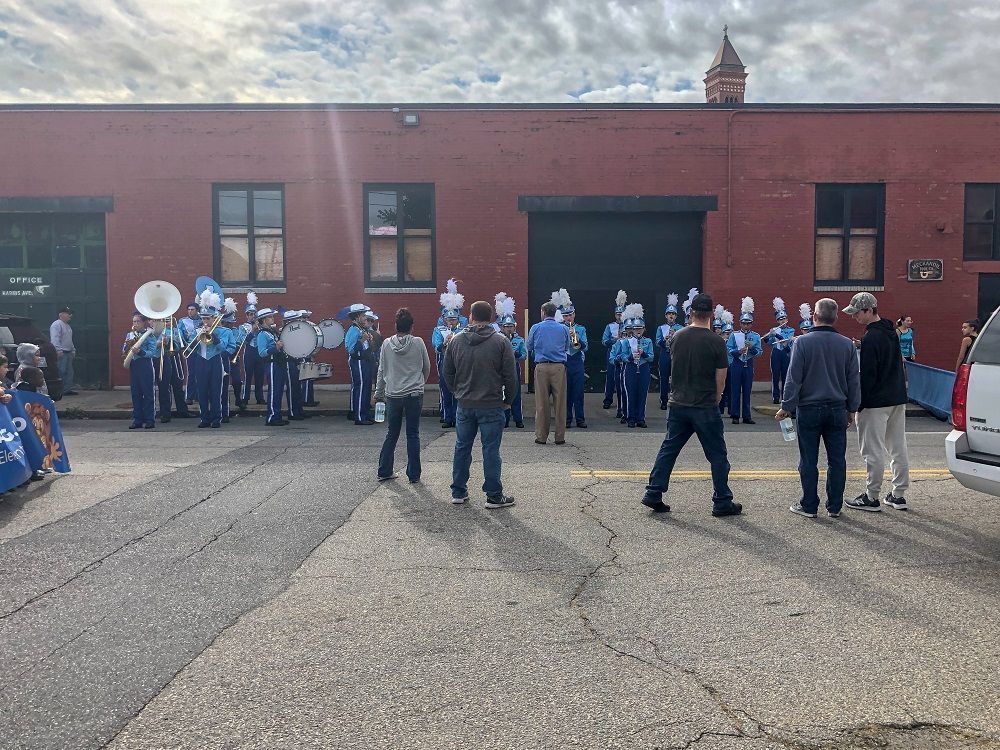 A high school marching band warms up before the parade
