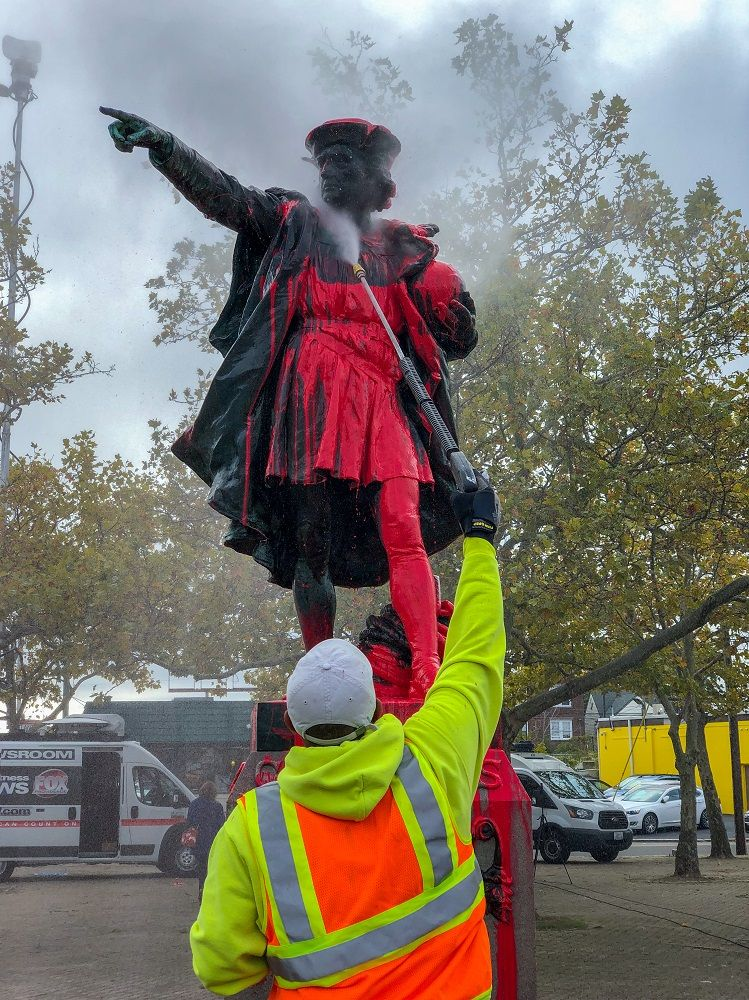 Working cleaning the Columbus statue