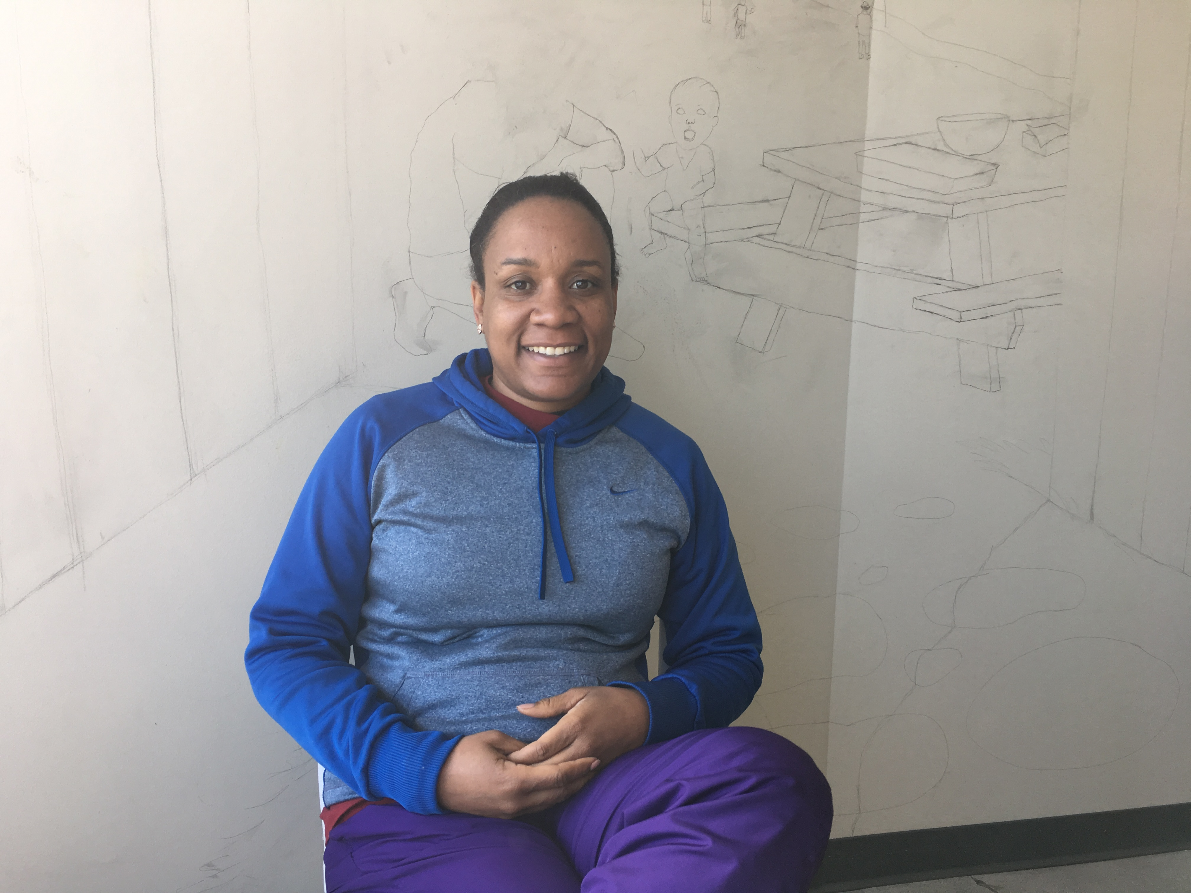 General Manager Janiqua Jackson sits in front of a mural in progress inside the community room at Urban Greens.
