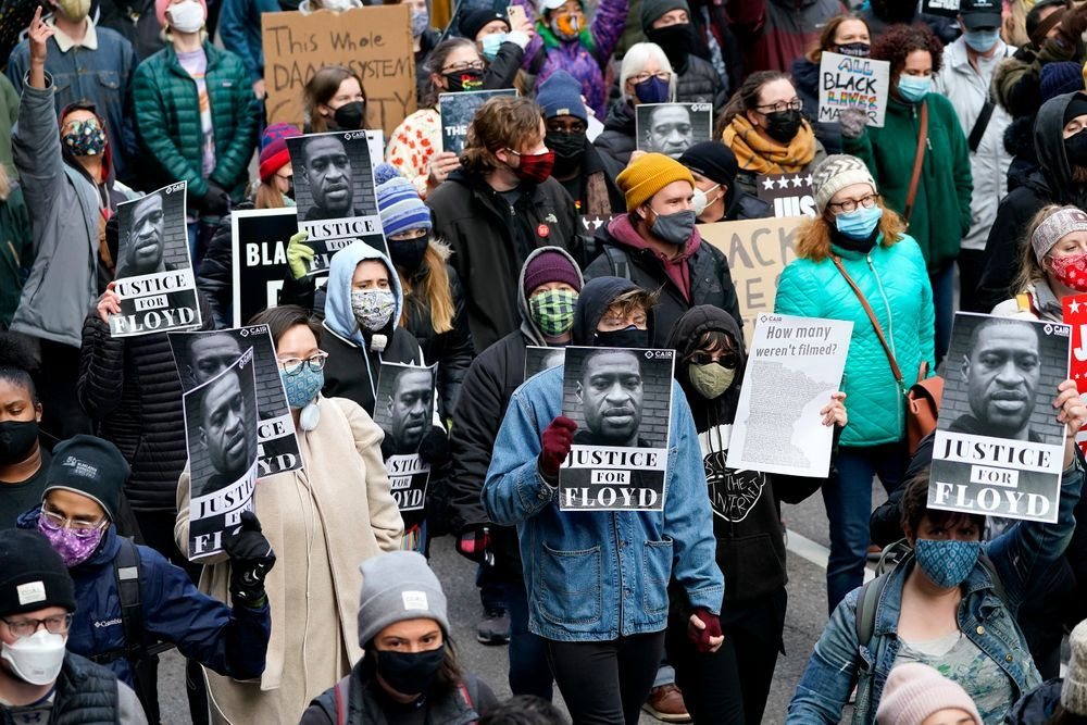 People hold signs as they march near the Hennepin County Government Center during a rally in Minneapolis on Monday, April 19, 2021, after the murder trial against former Minneapolis police Officer Derek Chauvin advanced to jury deliberations.