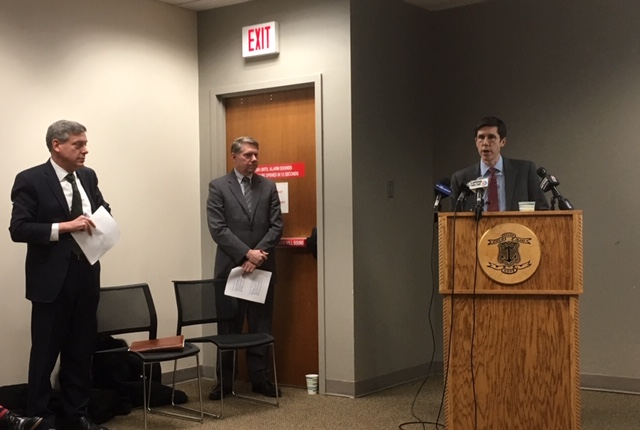 Raimondo Chief of Staff Brett Smiley (at podium) briefs reporters while Managment and Budget head Jonathan Womer and Budget Officer Tom Mullaney listen.