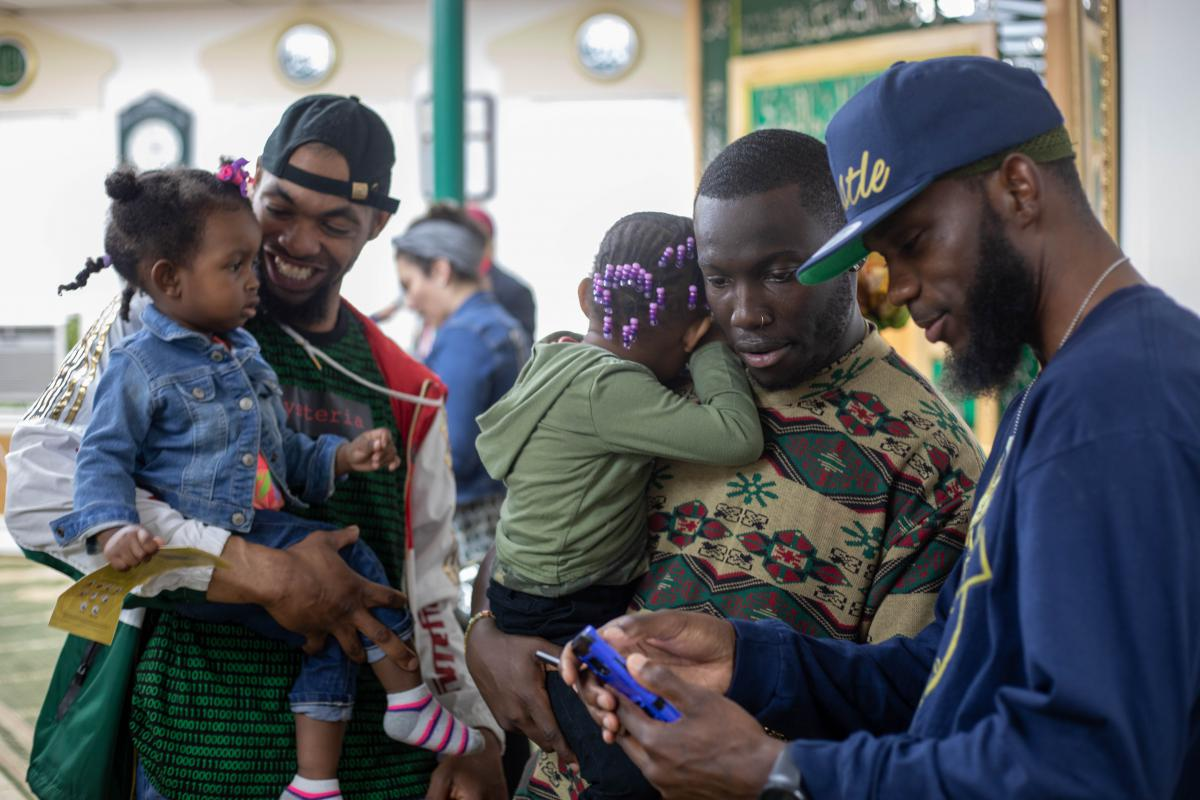 Saladin Hasan Jr. (center) holds his daughter while talking with his friends following the press conference.