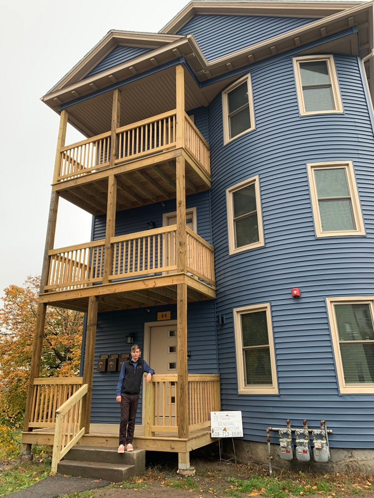 Taylor Bearden outside one of his renovated triple deckers in Worcester, Mass.