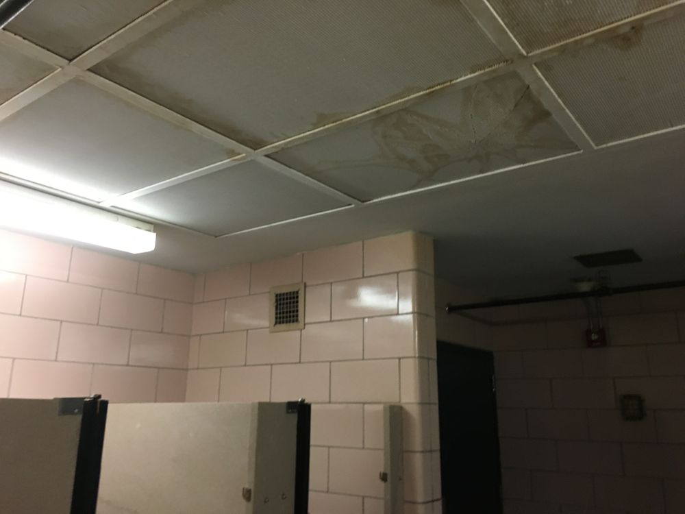A leak from the roof has damaged a light fixture in the ceiling of this bathroom.