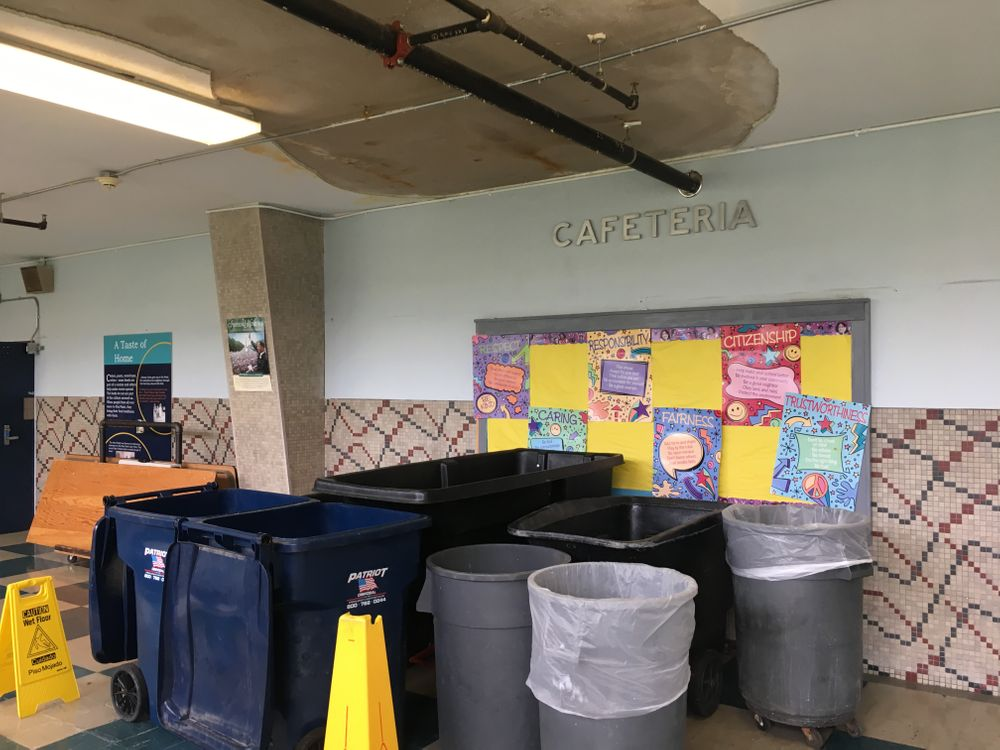Trash cans are permanently positioned in the hallway between the gym and cafeteria, under a leak in the school's roof.