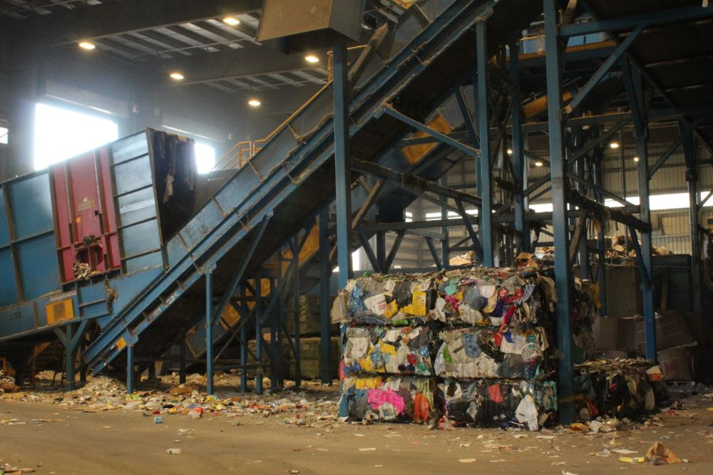 Bales of plastic sit on the floor of a materials recovery facility in Rochester, Mass.