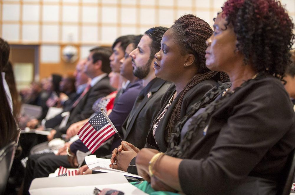 Marie Claire Kum, from Cameroon, holds a U.S. flag as she listens intently at the naturalization ceremony at the JFK Museum in Boston.