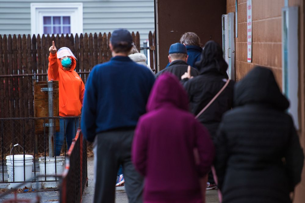 """Irma Resendiz, a """"health ambassador"""" for the City of Central Falls, directs people registered for appointments to get vaccinated to line up outside a clinic at the Knights of Columbus Hall."""