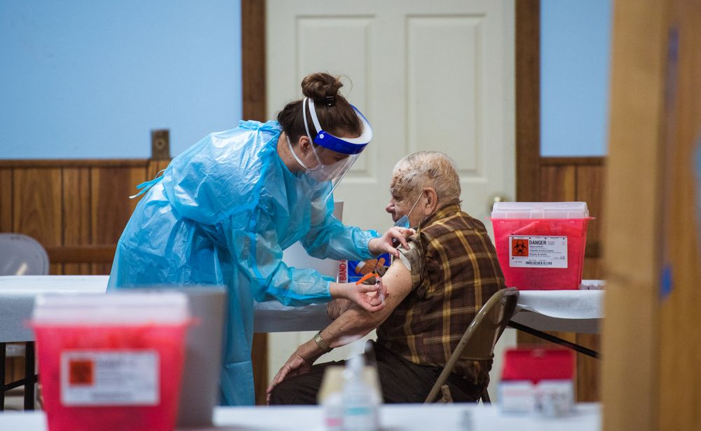 Michaela Young, a pharmacy student at the University of Rhode Island, administers a COVID-19 shot  to Maurice Landry, 79, of Central Falls.