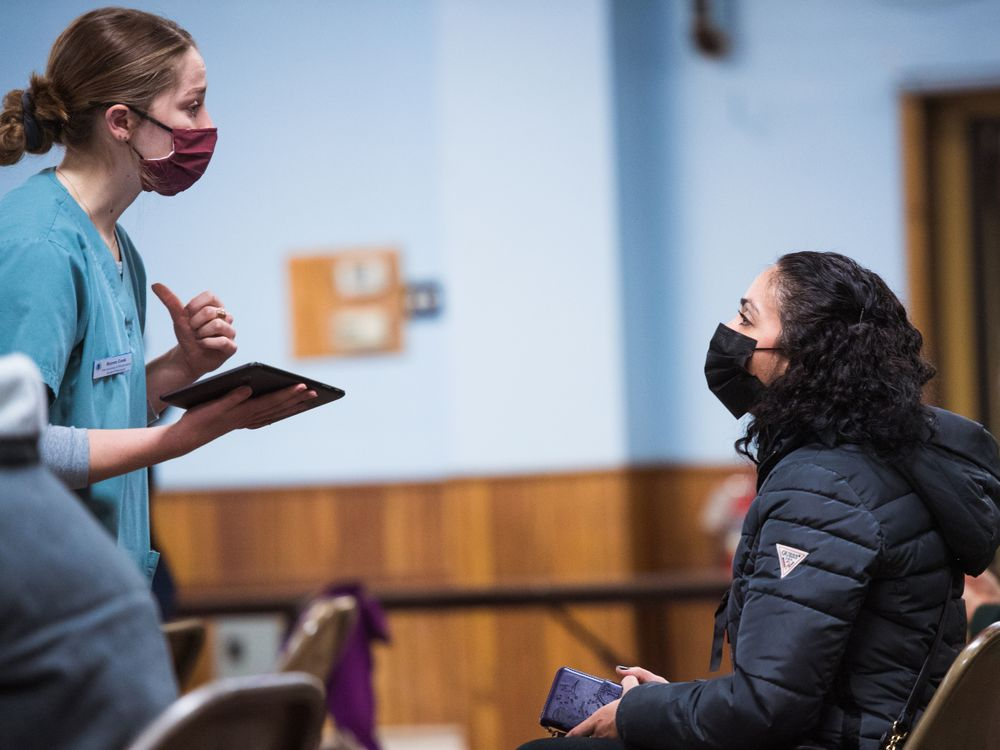 Gloria Arango, 43, a housekeeper in Central Falls and single mother, talks to Brynne Costa, a pharmacy student at the University of Rhode Island, after being vaccinated. Costa is among the volunteers who monitor people who are vaccinated in case of any reaction.