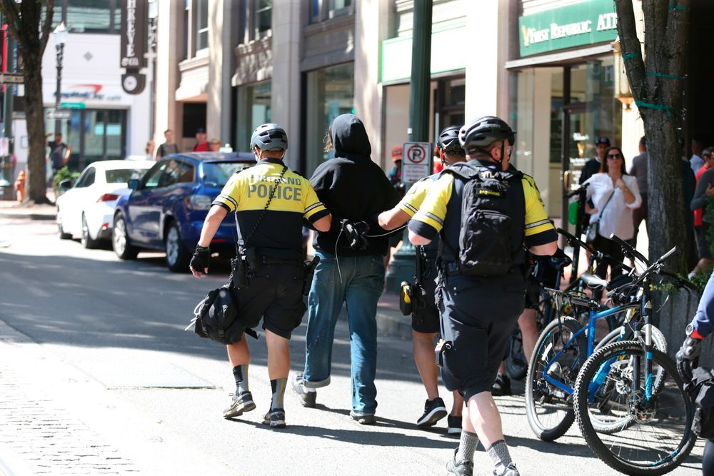 A protestor is taken into custody by police as demonstrators from at least three groups, including members of the so-called Proud Boys and anti-fascist groups, that had planned rallies or demonstrations at different sites in the city gathered, Saturday, June 29, 2019, in Portland, Ore. Competing demonstrations spilled into the streets of downtown Portland, with fights breaking out in places as marchers clashed. (Dave Killen/The Oregonian via AP)