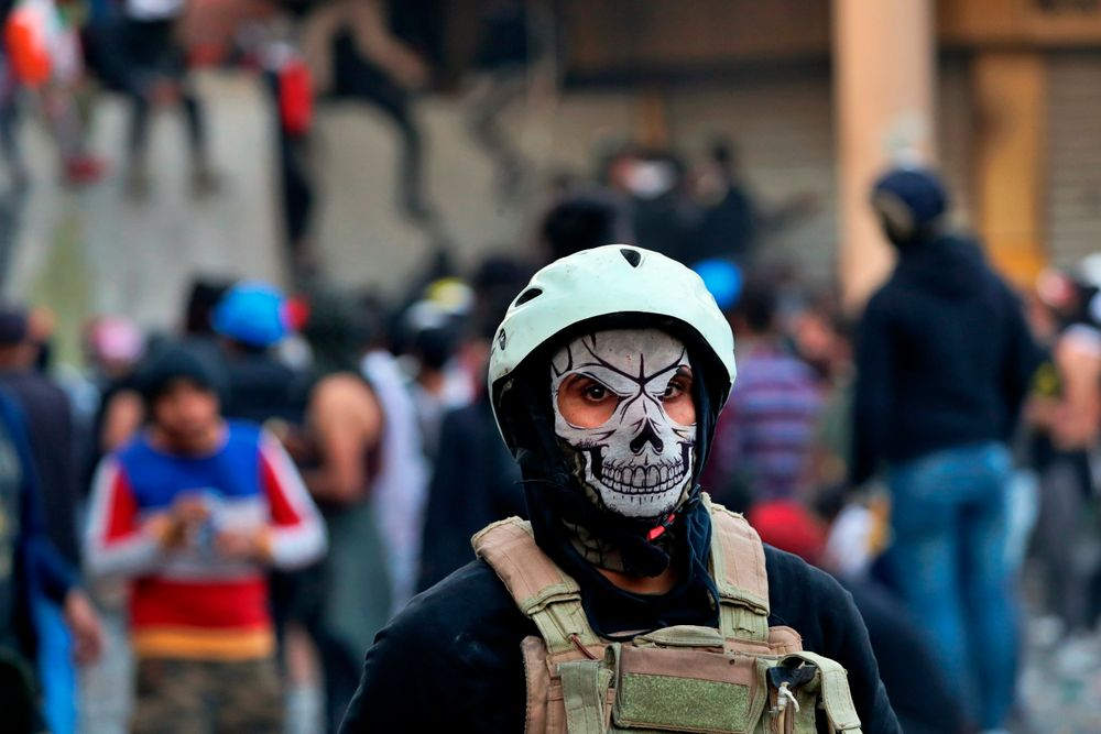 A protester wears a mask during clashes with security forces, in Baghdad, Iraq, Sunday, Nov. 24, 2019. At least sixteen people were killed and over 100 wounded in the renewed clashes, which kicked off Thursday as protesters tried to scale a concrete barrier on historic Rasheed Street prompting security forces to fire live ammunition, tear gas and rubber bullets to disperse them. (AP Photo/Khalid Mohammed)