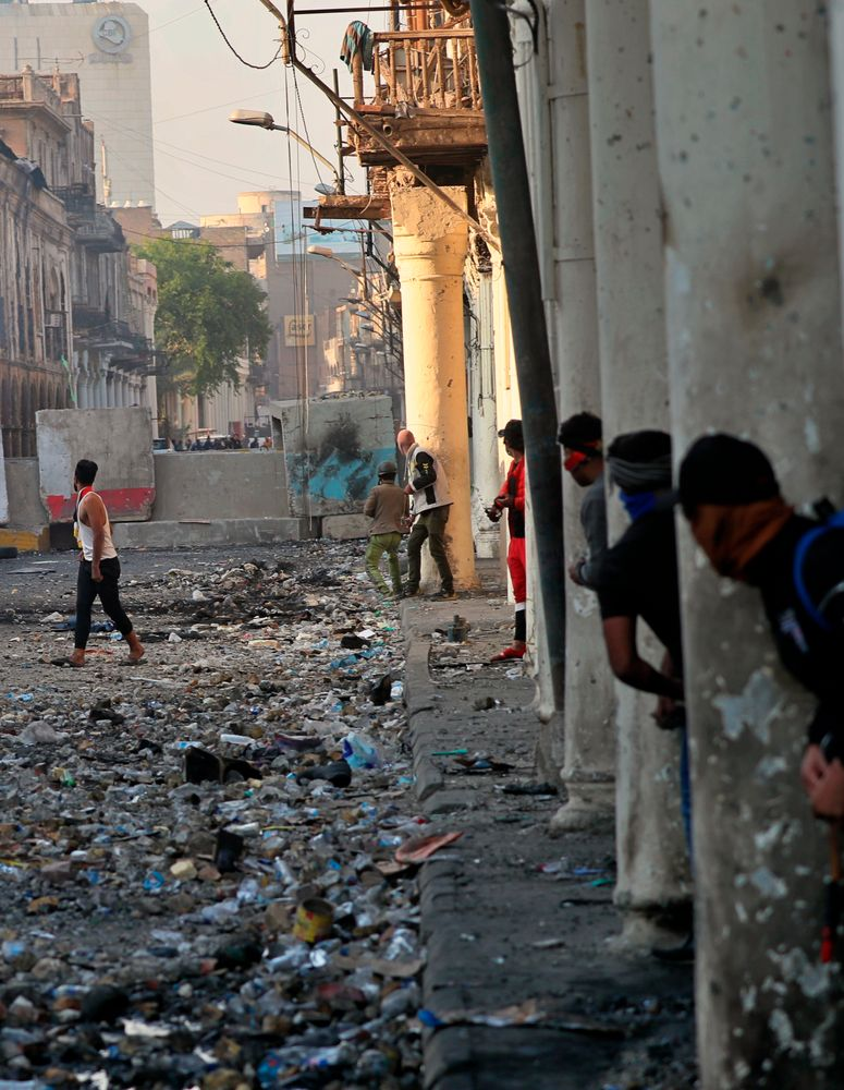 Demonstrators take cover during clashes between security forces and anti-government protesters in the historic Rasheed Street, Baghdad, Iraq, Sunday, Nov. 24, 2019. Hundreds of people have died since demonstrations began Oct. 1, when thousands of Iraqis, mostly youth, took to the streets to decry corruption and poor services. The leaderless uprising seeks to overthrow the political establishment. (AP Photo/Khalid Mohammed)