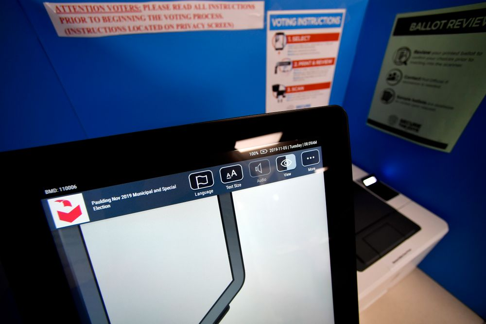 A touchscreen voting machine and printer are seen in a voting booth, Tuesday, Nov. 5, 2019, in Paulding, Ga. New voting machines that combine touchscreens with paper ballots are getting a limited test run in Georgia as officials rush to meet a court-ordered deadline to retire the old system before any votes are cast in 2020. (AP Photo/Mike Stewart)