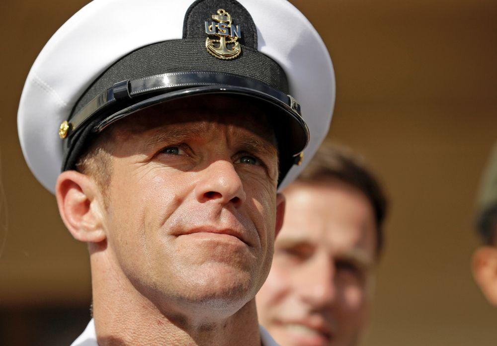 FILE - In this Tuesday, July 2, 2019, file photo, Navy Special Operations Chief Edward Gallagher leaves a military court on Naval Base San Diego. The attorney for Gallagher, convicted of posing with a dead captive in Iraq, says the Navy is trying to remove the special operations chief from the elite fighting force in retaliation for President Donald Trump restoring his rank. Defense attorney Timothy Parlatore said the Navy is holding a review board proceeding to remove Edward Gallagher's Trident pin and summoned him to meet with the SEAL leadership on Wednesday, Nov. 20, 2019. (AP Photo/Gregory Bull, File)