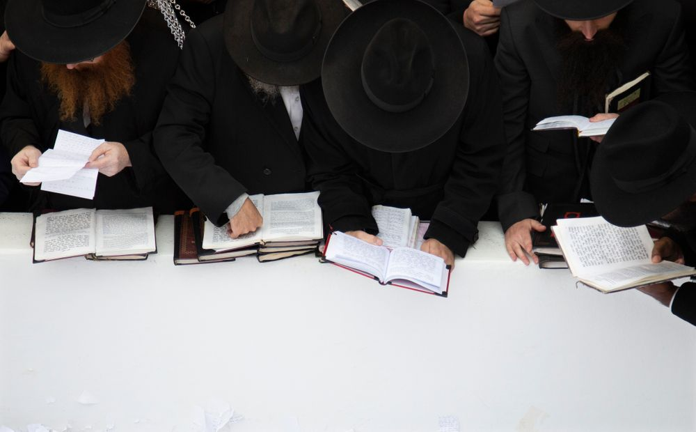 In this Nov. 22, 2019, photo, Hasidic leaders read personal notes and prayers at the resting place of the late Rabbi Menachem Mendel Schneerson, known as the Lubavitcher Rebbe, while attending the annual International Conference of Chabad-Lubavitch Emissaries at Montefiore Cemetery in New York. The annual conference included seminars, a class photo of about 5,800 rabbis in attendance and an evening dinner. (AP Photo/Jessie Wardarski)