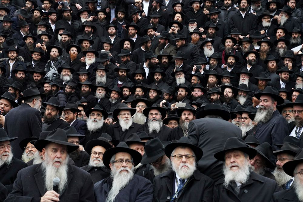 In this Nov. 24, 2019, photo, Hasidic leaders gather for an annual group photo outside of the Chabad-Yubavitch Worldwide headquarters as a part of the International Conference of Chabad-Lubavitch Emissaries in New York. The annual conference included seminars, a class photo of about 5,800 rabbis in attendance and an evening dinner. (AP Photo/Emily Leshner)