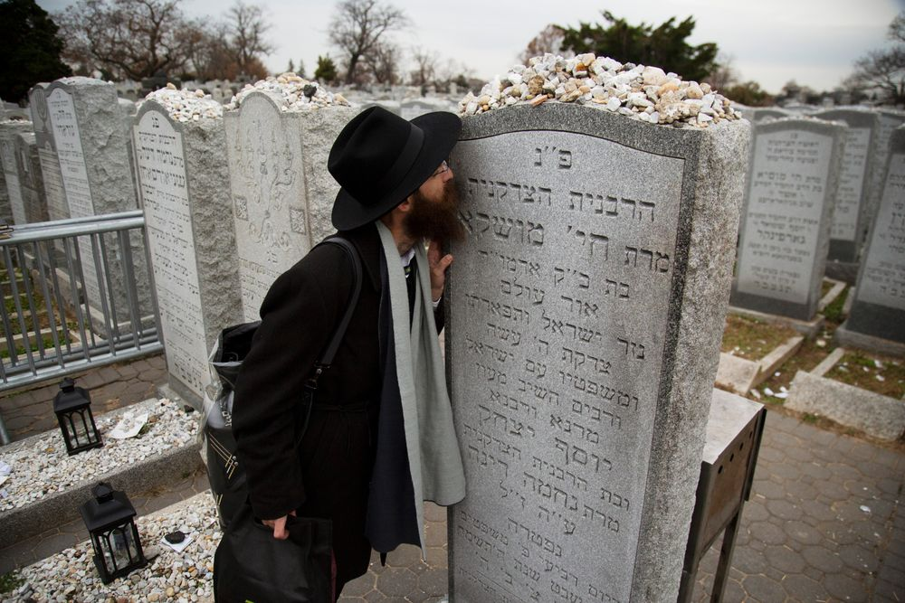 In this Nov. 22, 2019, photo, a rabbi kisses the headstone of Chaya Mushka Schneerson, the wife of Rabbi Menachem Mendel Schneerson, known as the Lubavitcher Rebbe, while attending the annual International Conference of Chabad-Lubavitch Emissaries at Montefiore Cemetery in New York. The annual conference included seminars, a class photo of all 5,800 rabbis in attendance and an evening dinner. (AP Photo/Jessie Wardarski)