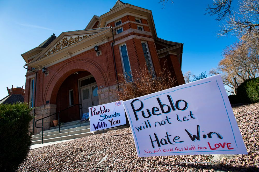 Signs, flowers and candles expressing love for the Jewish community stand outside the Temple Emanuel in Pueblo, Colo., Tuesday, Nov. 5, 2019. Richard Holzer, 27, of Pueblo was arrested Friday by the FBI after he allegedly said he was going to go blow up the temple because he hates Jews. Temple president Michael Atlas-Acuña found the items when he arrived in the morning. (Christian Murdock/The Gazette via AP)