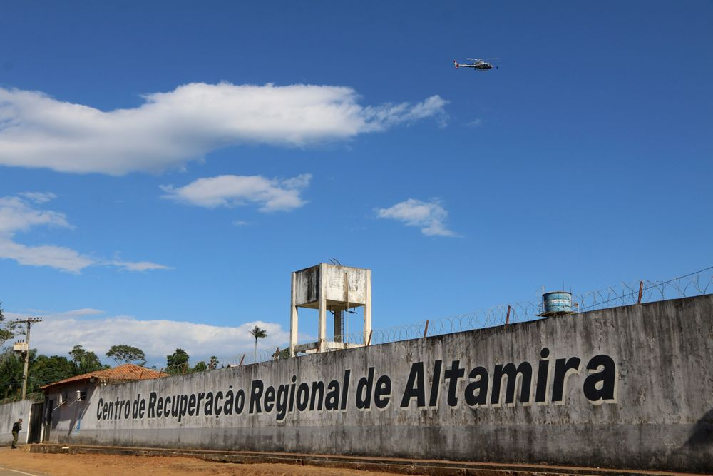 A police helicopter flies over the Regional Recovery Center, a prison, in Altamira, Para state, Brazil, Monday, July 29, 2019. Authorities say at least 52 prisoners were killed by other inmates during a riot, and that some of the victims were decapitated while others asphyxiated. (Wilson Soares/Panamazonica via AP)