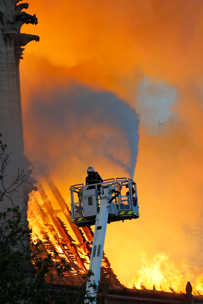 A fire fighter uses a hose as Notre Dame cathedral is burning in Paris, Monday, April 15, 2019. A catastrophic fire engulfed the upper reaches of Paris' soaring Notre Dame Cathedral as it was undergoing renovations Monday, threatening one of the greatest architectural treasures of the Western world as tourists and Parisians looked on aghast from the streets below. (AP Photo/Francois Mori)