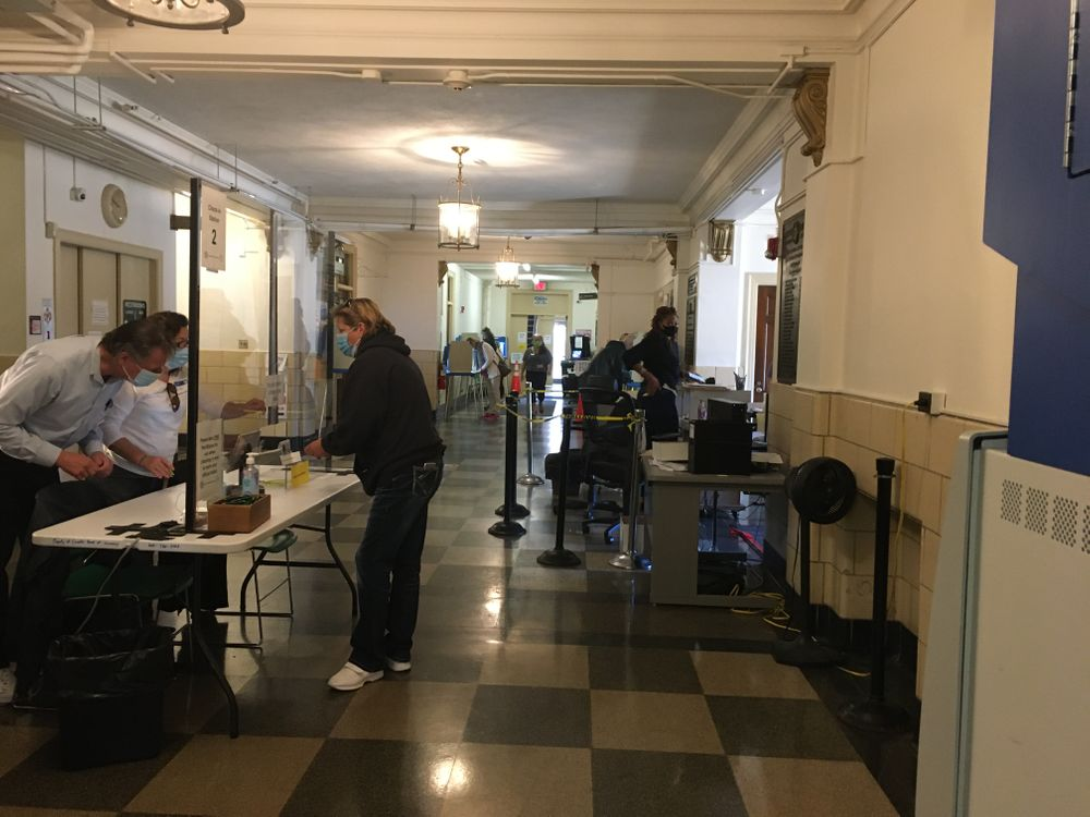 Poll workers check in a voter inside Cranston City Hall.