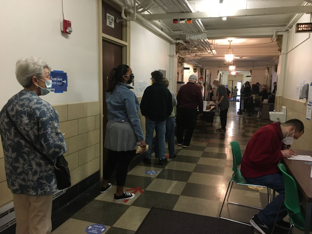 Cranston voters wait to be checked in for early voting.
