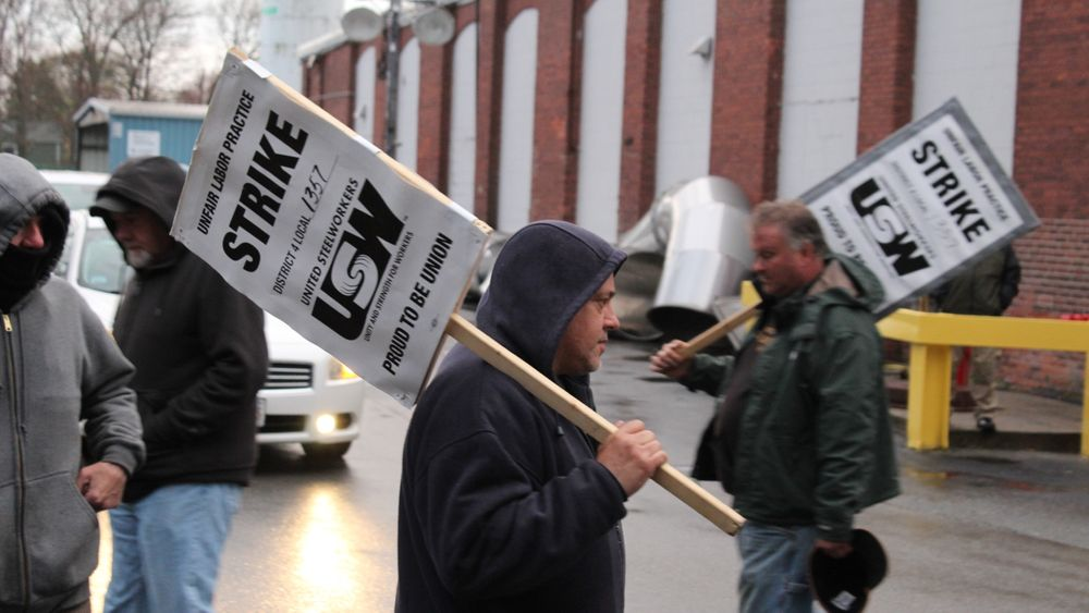 Union members hold up replacement workers leaving the ATI plant in New Bedford.