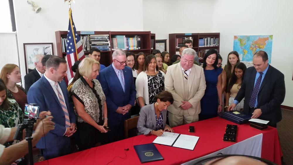 Rhode Island Governor Gina Raimondo signs education reform bills into law.