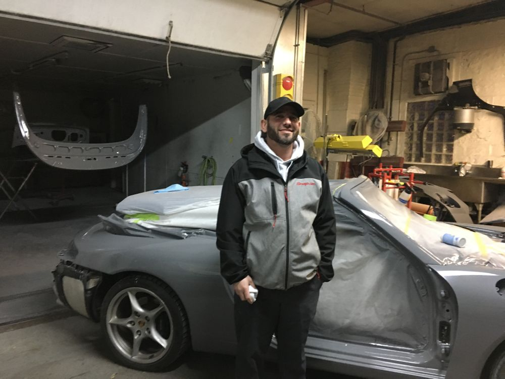Warren Auto Body owner Steven Pimentel stands in front of a friend's freshly painted car.