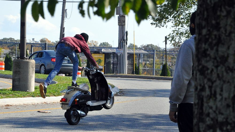 Moped rider Chase performs a stunt near Reservoir Avenue in Providence on Thursday, Oct. 22, 2020.