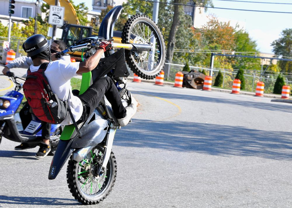 A dirt bike rider does a wheelie near Reservoir Avenue in Providence on Thursday, Oct. 22, 2020.